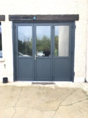 porte de garage en aluminium repliable trois vantaux avec portillon de service